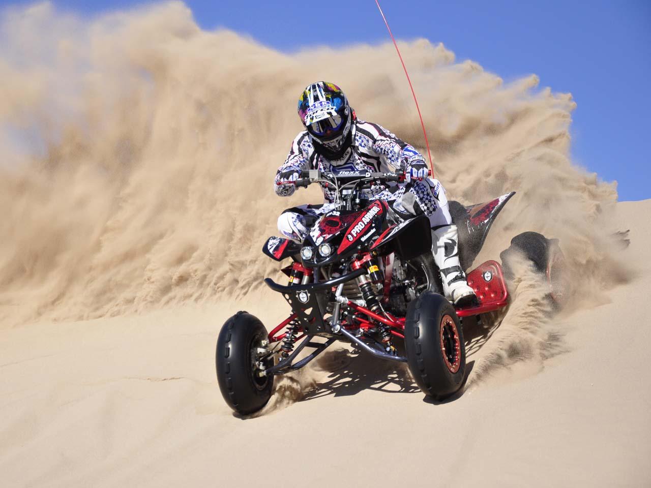 2010.honda_.trx450r.front-left.black_.riding.on-sand.jpg