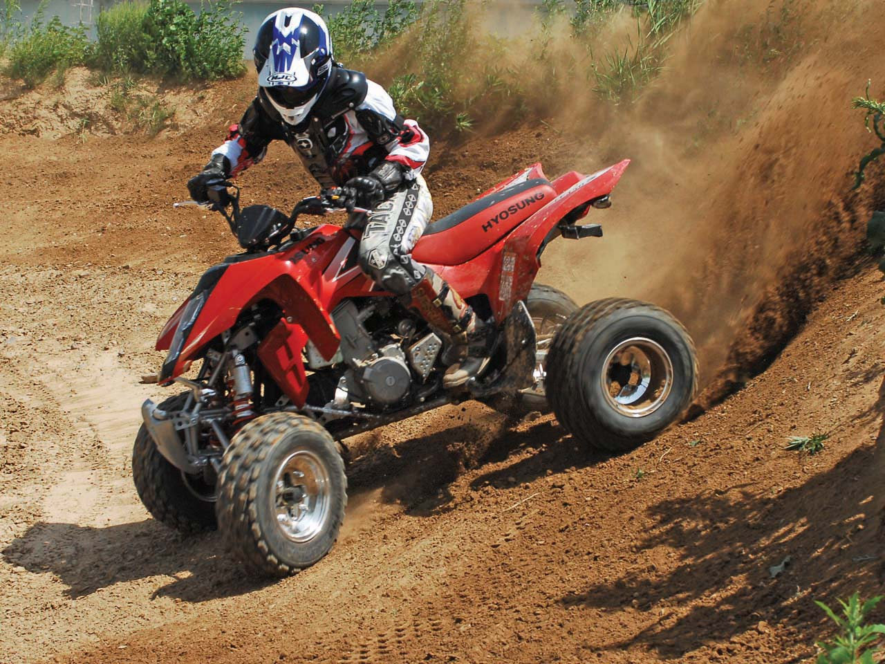 2010.hyosung.te450s.red_.left_.riding.on-sand.jpg