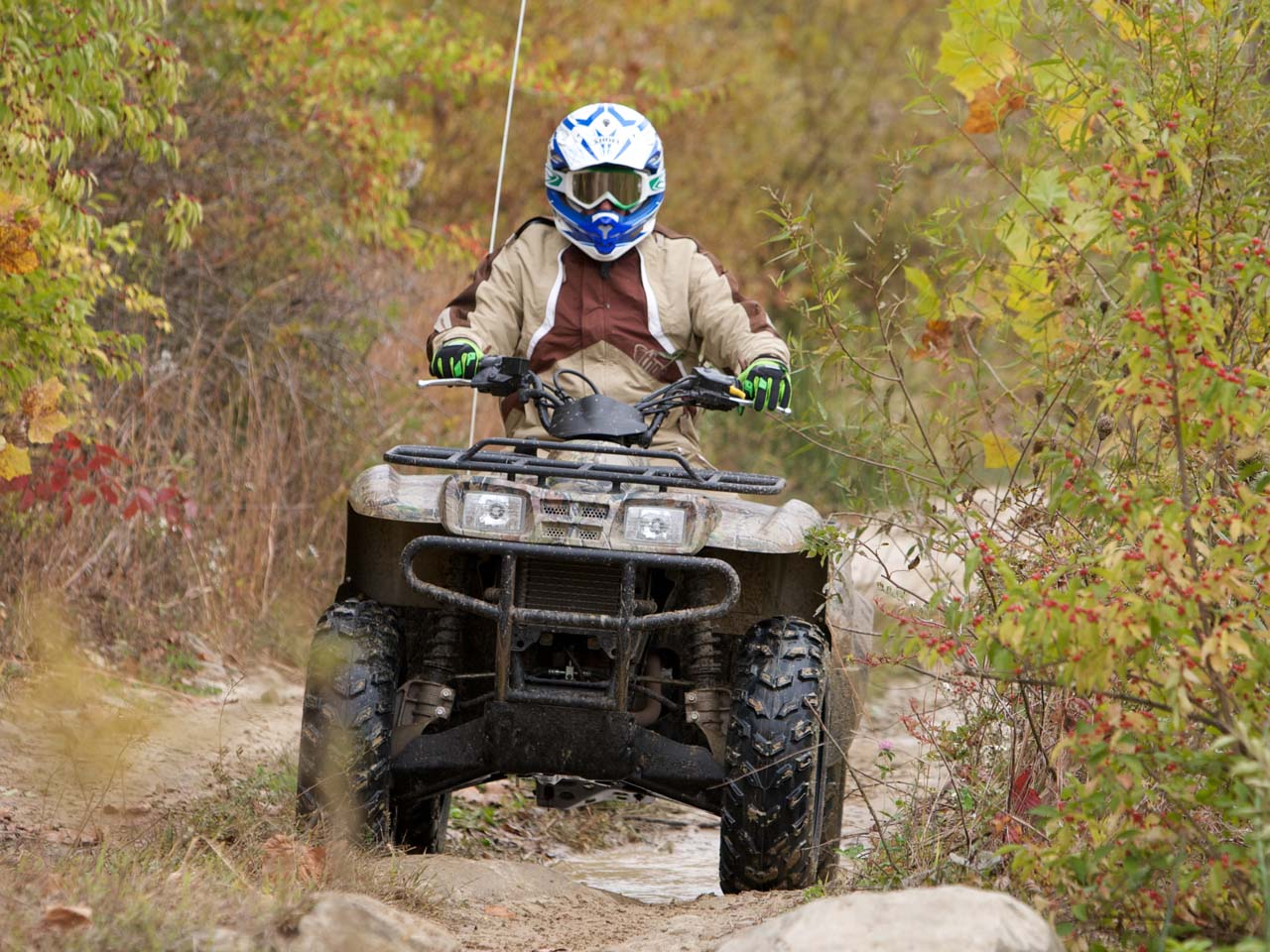 2010.kawasaki.prairie360-4x4.camo_.front_.riding.on-trail_1.jpg