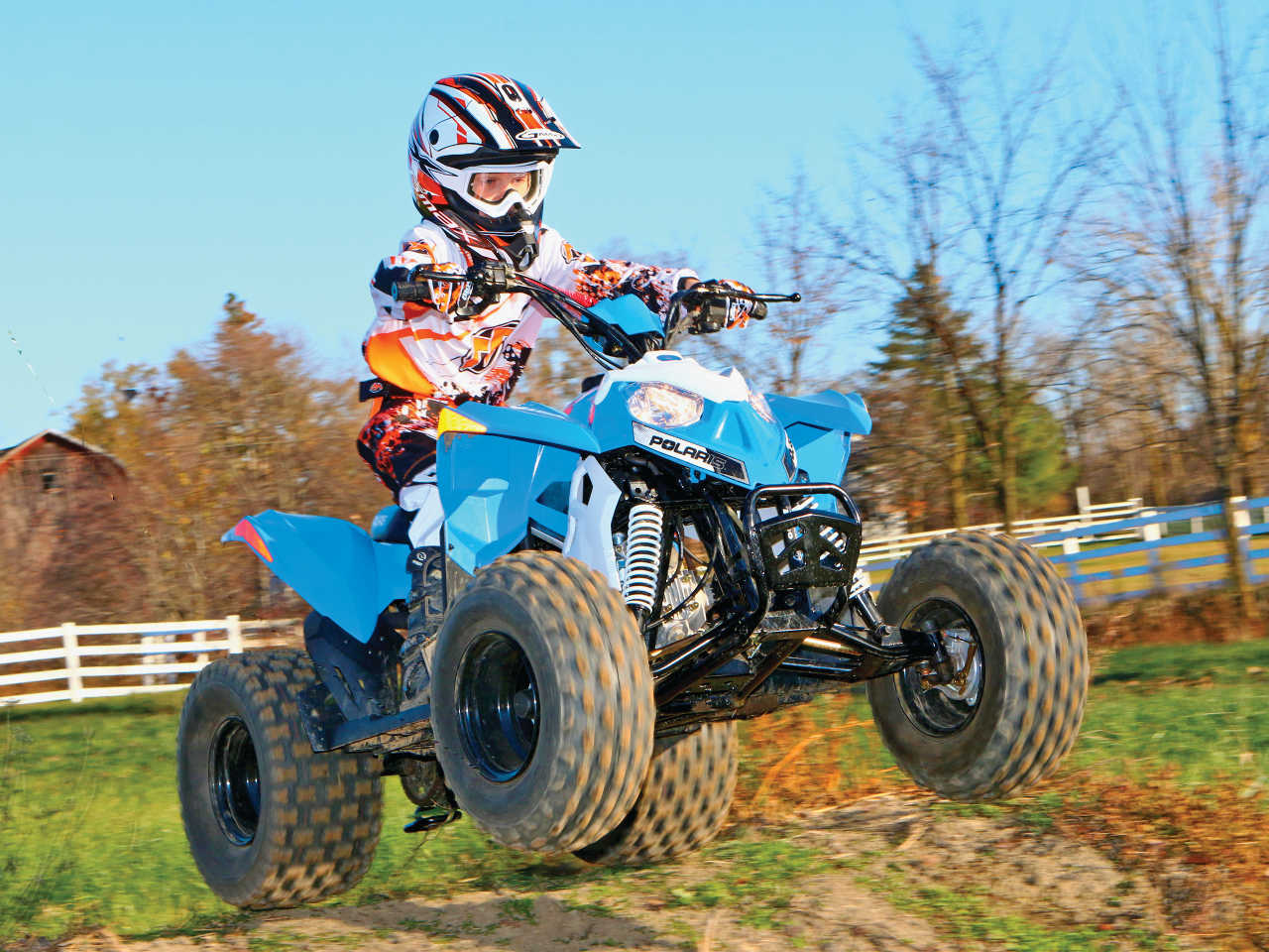 2014.polaris.outlaw90.front right.blue_.jumping.in air mini quad test the polaris outlaw 90 atv illustrated