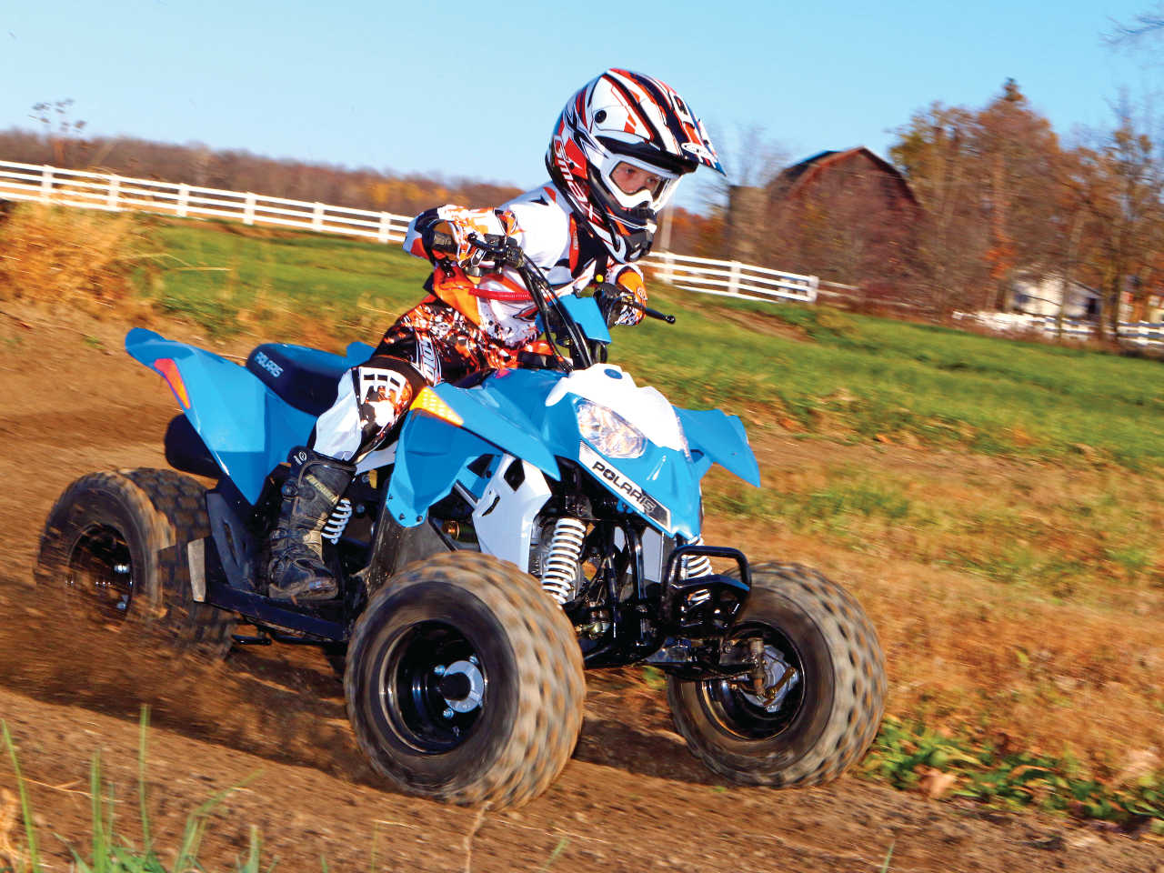 2014.polaris.outlaw90.front-right.blue_.riding.on-dirt.jpg