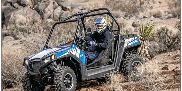 2015.polaris.rzr570efi-custom-mike-young.blue.front-left.riding.on-dirt.jpg