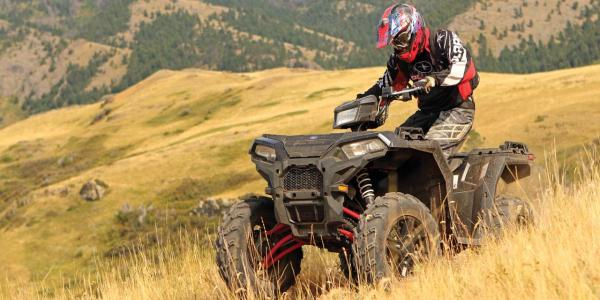 2017.polaris.sportsman-xp1000.green.front-left.riding.in-field.jpg