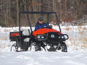 2010.husqvarna.huv4414g-xp.orange.front-right.riding.on-snow.jpg