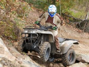 2010.kawasaki.prairie360-4x4.camo_.front-left.riding.over-rocks.jpg