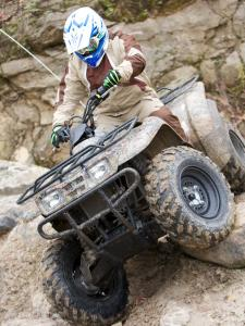 2010.kawasaki.prairie360-4x4.camo_.front_.riding.over-rocks.jpg
