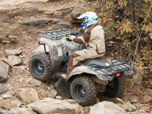 2010.kawasaki.prairie360-4x4.camo_.rear-left.riding.over-rocks.jpg