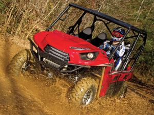 2012.kawasaki.teryx4.red.front-left.riding.through-mud.jpg