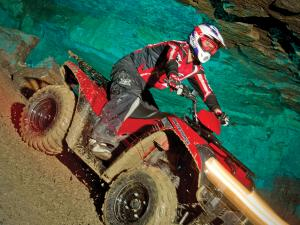 2012.kawsaki.brute-force300.red_.front-right.riding.in-cave.jpg
