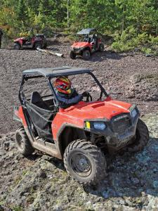 2012.polaris.rzr570.red_.front-right.riding.on-rocks.jpg
