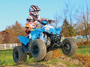 2014.polaris.outlaw90.front-right.blue.jumping.in-air.jpg