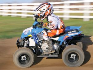 2014.polaris.outlaw90.left.blue.riding.on-dirt.jpg