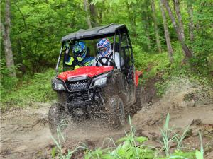 2015.honda.pioneer500.red.front-left.riding.through-mud.JPG