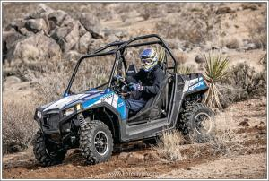 2015.polaris.rzr570efi-custom-mike-young.blue_.front-left.riding.on-dirt.jpg