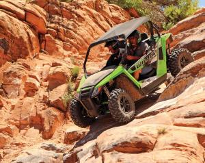 2017.arctic-cat.wildcat-trail.black-and-green.front-left.riding.down-rocks.jpg