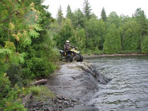 location.2011.atv-nation.atv-parked-on-rocks-by-water.jpg