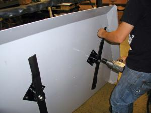 vendor.2011.kunz-engineering.pull-behind-mower.close-up.installing-blades.jpg