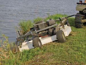 vendor.2011.kunz-engineering.pull-behind-mower.cutting-grass.by-lake.jpg
