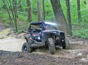vendor.quadboss.446-radial-tire.on-polaris-rzr.riding-through-mud.jpg